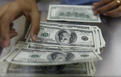 Женщина пересчитывает долларовые купюры в пункте обмена валюты в Янгоне 23 мая 2013 года. Доллар растет с двухмесячного минимума к иене, а австралийский доллар подешевел после выхода слабых показателей Китая - крупнейшего экспортного рынка Австралии. REUTERS/Soe Zeya Tun