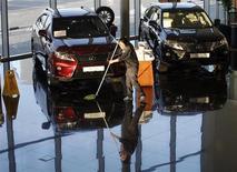 Уборщица моет пол в салоне Lexus в Красноярске 6 февраля 2013 года. Продажи автомобилей в РФ снизились в мае 2013 года на 12 процентов в годовом исчислении до 229.670 штук, сообщила в понедельник Ассоциация европейского бизнеса (АЕБ). REUTERS/Ilya Naymushin