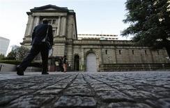 Человек идет в сторону здания Банка Японии в Токио 20 ноября 2012 года. Банк Японии во вторник сохранил монетарную политику без изменений и воздержался от новых мер, направленных на сокращение рыночной волатильности, вероятно, рассудив, что недавнее беспокойство на рынках еще не представляет значительной угрозы для экономики. REUTERS/Yuriko Nakao