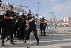 Полицейские стреляют из водометов и распыляют слезоточивый газ для разгона демонстрантов с площади Таксим в Стамбуле 11 июня 2013 года. Сотни полицейских заполнили стамбульскую площадь Таксим во вторник утром впервые после начала массовых протестов, разогнав демонстрантов при помощи водяных пушек и слезоточивого газа. REUTERS/Yannis Behrakis