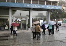 Люди проходят мимо отделения Bank of Cyprus в Никосии 18 апреля 2013 года. Генеральный прокурор Кипра проведет расследование обстоятельств покупки кипрским банком Bank of Cyprus маленького российского банка в 2008 году, сообщили власти во вторник. REUTERS/Andreas Manolis