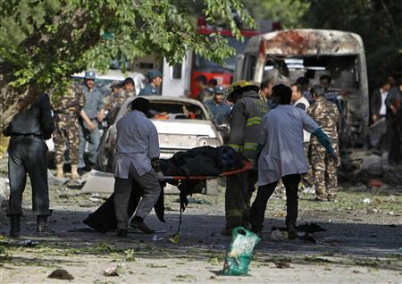 Men carry a victim of a suicide car bomb attack in Kabul June 11, 2013. A loud explosion was heard in the Afghan capital Kabul's diplomatic area, and a police source said it was a suicide attack not far from the U.S. Embassy. REUTERS/Omar Sobhani