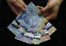 The new Canadian five and 10 dollar bills, made of polymer, are displayed with the previously released 20, 50 and 100 dollar notes following an unveiling ceremony at the Bank of Canada in Ottawa April 30, 2013. REUTERS/Chris Wattie