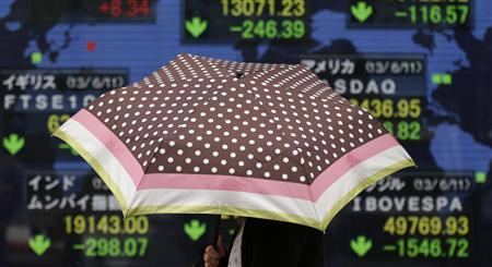 A woman with an umbrella walks past a stock index board showing various countries' stock price index outside a brokerage in Tokyo June 12, 2013. REUTERS/Toru Hanai