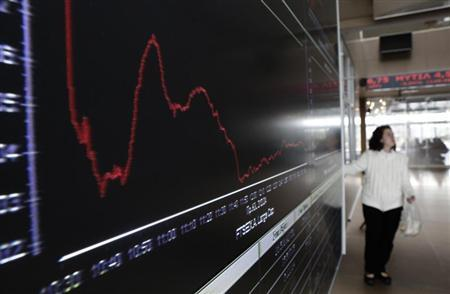 A woman stands next to an electronic board at the reception hall of the Athens stock exchange March 19, 2013. REUTERS/John Kolesidis