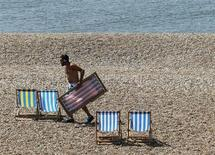 An attendant sets out deckchairs on a sunny day on Brighton Beach in southern England June 5, 2013. REUTERS/Luke MacGregor