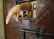 A prisoner puts his arm through the door of his cell in the historic Regina Coeli or Queen of Heaven jail in Rome June 6, 2013. REUTERS/Tony Gentile