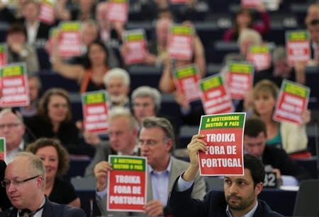 Members of the European Parliament hold posters with the slogan ''Troika away from Portugal'' during Portugal's President Anibal Cavaco Silva (not pictured) address to the assembly in Strasbourg, June 12, 2013. REUTERS/Vincent Kessler