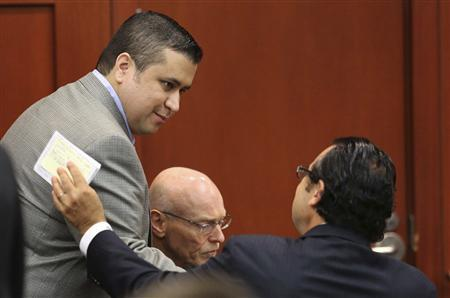 George Zimmerman is welcomed to the defense table by jury consultant Robert Hirschhorn (R) with defense co-counsel Don West on the third day of jury selection in his murder trial for the shooting death of Trayvon Martin, at Seminole circuit court in Sanford, Florida, June 12, 2013. REUTERS/Joe Burbank/Pool