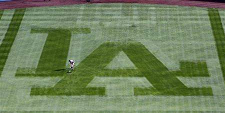 A Los Angeles Dodgers grounds crewman sweeps away the dew from the centerfield grass to prepare the field to play against the San Francisco Giants in the opening game of the MLB National League baseball season in Los Angeles, California April 1, 2013. REUTERS/Alex Gallardo