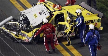 Jason Leffler is pulled from his number 18 Toyota after a crash in the NASCAR Camping World Series NextEra Energy Resources 250 truck race at the Daytona International Speedway in Daytona Beach, Florida, February 24, 2012. REUTERS/Pierre Ducharme