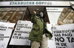 A masked demonstrator leaves a Starbucks coffee shop in central London December 8, 2012. REUTERS/Luke MacGregor