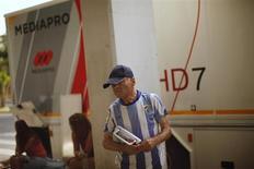 Canal+, la división de televisión de pago de Prisa, dijo el jueves que ha retenido el pago a Mediapro de 22 millones de euros correspondientes a la última factura de los derechos de fútbol de la temporada actual por considerar elevado el importe exigido. En la imagen, un seguidor de Málaga junto a un camión de Mediapro en el estadio de La Rosaleda, Málaga, el 11 de agosto de 2012. REUTERS/Jon Nazca