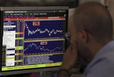 A trader looks at his screen on the Unicredit Bank trading floor in downtown Milan June 13, 2013. World shares fell and the dollar slumped on Thursday as a sell-off on global financial markets accelerated on concerns over whether central banks will continue the stimulus they have come to rely on. REUTERS/Alessandro Garofalo