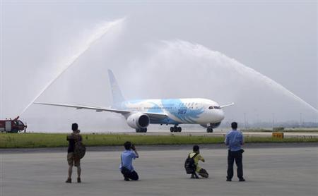 Journalists take pictures as China's first Boeing 787 Dreamliner belonging to China Southern Airlines is given a water cannon salute when the plane arrives at an airport in Guangzhou, Guangdong province June 2, 2013. REUTERS/China Daily/Files