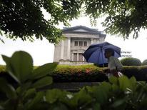 Пешеход проходит мимо здания Банка Японии в Токио 11 июня 2013 года. Ограничение количественного смягчения до двух лет может помочь стабилизировать долговой рынок, поскольку информация Центробанка о его монетарной политике, возможно, действительно повышает волатильность облигаций, заявил один из членов Банка Японии на заседании 21-22 мая. REUTERS/Yuya Shino