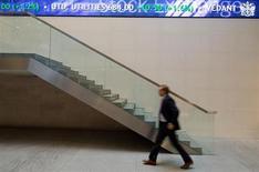 Человек проходит мимо электронного табло на Лондонской фондовой биржи 2 января 2013 года. Европейские рынки акций открылись ростом. REUTERS/Paul Hackett