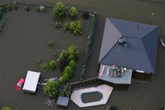 Une maison du village de Fichbeck en Allemagne sous les eaux, après le débordement de l'Elbe. Allianz a estimé vendredi que les inondations en Europe centrale lui coûteraient 350 millions d'euros, compte tenu du transfert de près d'un tiers du fardeau aux réassureurs. Le premier assureur européen versera 500 millions d'euros à ses assurés, et environ 150 millions d'euros seraient à la charge des réassureurs. /Photo prise le 12 juin 2013/REUTERS/Thomas Peter