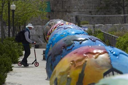 A man rides a scooter near giant globes displayed outside the walls of Jerusalem's Old City April 17, 2013. REUTERS/Ronen Zvulun/Files