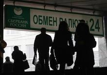 Люди проходят под рекламой Сбербанка в Москве 18 ноября 2009 года. Рубль подорожал к бивалютной корзине до уровней, где ЦБ снижает объемы валютных интервенций, благодаря восстановлению спроса на высокорискованные активы после их существенного падения, за счет дорожающей нефти и в преддверии налогового периода, когда экспортеры увеличивают объемы продаж валютной выручки. REUTERS/Denis Sinyakov