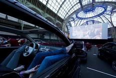 Visitors watch a film as they attend the opening night of a drive-in cinema, which will run till June 21, at the Grand Palais in Paris June 11, 2013. REUTERS/Gonzalo Fuentes