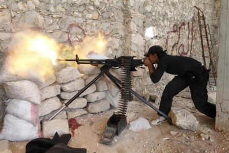 A Free Syrian Army fighter shoots his weapon near Kindi hospital, which is under the control of forces loyal to President Bashar Al-Assad, as both sides fight to take control of the hospital in Aleppo June 11, 2013. REUTERS/Hamid Khatib