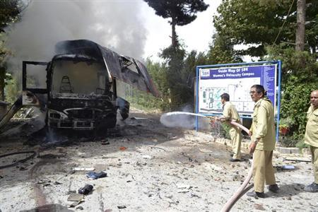 Firefighters spay water to extinguish fire from a burning bus at the site of a bomb blast in Quetta June 15, 2013. REUTERS/Naseer Ahmed