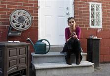 Viktoria Mohacsi sits at the door of the house, where she rents the basement apartment, in Toronto, May 9, 2013. REUTERS/Mirjam Donath