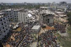 Crowds gather at the collapsed Rana Plaza building as people rescue garment workers trapped in the rubble, in Savar, 30 km (19 miles) outside Dhaka in this April 24, 2013 file photo. REUTERS/Andrew Biraj/Files