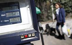 Женщина проходит мимо заправки в Риме, 13 марта 2012 года. Цены на нефть снижаются за счет высоких запасов топлива в США и низких прогнозов мирового потребления. REUTERS/Tony Gentile
