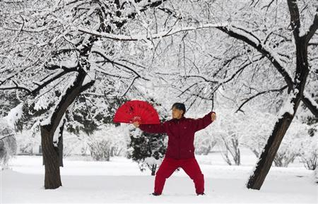 A woman practices tai chi with a fan after a snowfall in Shenyang, Liaoning province April 8, 2013. REUTERS/Stringer