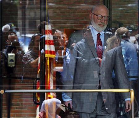 Reporters and television cameras are reflected in the glass doors as J.W. Carney, defense attorney for accused mob boss James ''Whitey'' Bulger, leaves the U.S. Federal Courthouse at the end of first day of Bulger's trial in Boston, Massachusetts June 12, 2013. REUTERS/Brian Snyder