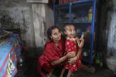 Rashida Begum, who survived from the rubble of collapsed Rana Plaza Building plays with her daugther inside her slum house in Savar June 4, 2013. REUTERS/Andrew Biraj