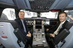French Prime Minister Jean-Marc Ayrault (L) and Airbus President and CEO Fabrice Bregier pose in an Airbus A350 passenger aircraft cockpit replica during the opening visit of the 50th Paris Air Show, at Le Bourget airport near Paris, June 17, 2013. The air show runs from June 17 to 23. REUTERS/Philippe Wojazer