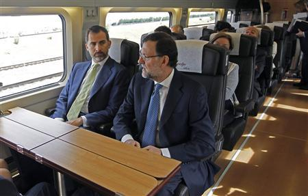 Spain's Crown Prince Felipe rides next to Spain's Prime Minister Mariano Rajoy (R) during the inaugural trip of Spain's newest AVE high speed train service from Madrid to Alicante, eastern Spain June 17, 2013. REUTERS/J.J. Guillen/Pool
