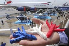 An Airbus employee presents three model airplanes in blue, white and red, made from starch using a 3D printing technique during the opening of 50th Paris Air Show, at the Le Bourget airport near Paris, June 17, 2013.REUTERS/Pascal Rossignol