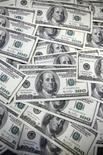 Долларовые купюры в банке в Сеуле 20 сентября 2011 года. Доллар США держится выше двухмесячного минимума к иене, но его рост затруднен опасением, что ФРС намекнет на завершение стимулирующей программы. REUTERS/Lee Jae-Won