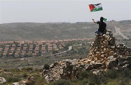 A protester waves a Palestinian flag in front of the Jewish settlement of Ofra during clashes near the West Bank village of Deir Jarir near Ramallah April 26, 2013. REUTERS/Mohamed Torokman