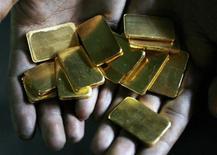 Работник аффинажного завода в Бомбее держит слитки золота 3 марта 2008 года. Цены на золото снижаются на фоне пониженного спроса на физическом рынке и опасений, что ФРС сократит объем скупки облигаций. REUTERS/Arko Datta
