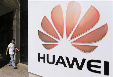 A man walks past a Huawei company logo outside the entrance of a Huawei office in Wuhan, Hubei province October 9, 2012. REUTERS/Stringer/Files