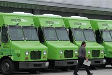 A worker walks past Amazon Fresh delivery vans parked at an Amazon Fresh warehouse in Inglewood, California, June 14, 2013. REUTERS/Jonathan Alcorn