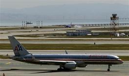 An American Airlines passenger jet taxis to a runway as a Southwest Airlines jet (rear) lands at San Francisco International Airport in San Francisco, California April 22, 2013. REUTERS/Robert Galbraith