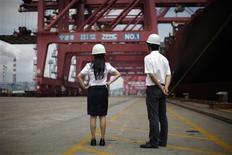 Employees stand next to a container ship at Ningbo port in Ningbo, Zhejiang province in this June 21, 2012 file photo. REUTERS/Carlos Barria/Files