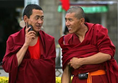 Tibetan monks use their mobile phones in Lhasa, Tibet July 3, 2006. REUTERS/Joe Chan/Files