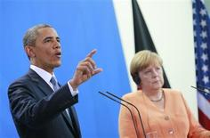 U.S. President Barack Obama speaks next to German Chancellor Angela Merkel (R) during a news conference after their meeting at the Chancellery in Berlin June 19, 2013. REUTERS/Thomas Peter
