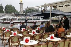 People sit at a terrace cafe near the Alexandre III bridge on the opening day of the new pedestrian walkway area between the Orsay Museum and Alma Bridge on the left bank of the River Seine in Paris June 19, 2013. REUTERS/Charles Platiau
