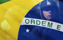 Manifestante é visto atrás da bandeira do Brasil durante protestos contra serviços públicos em São Paulo nesta quarta-feira. 19/06/2013 REUTERS/Alex Almeida