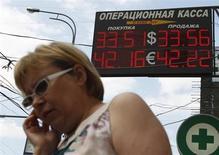 Женщина проходит мимо пункта обмена валют в Москве 22 июня 2012 года. Рубль упал на годовой минимум к корзине валют, отражая повсеместный выход из рискованных и сырьевых активов и спрос на доллар США после заявленных Федрезервом намерений начать сокращение стимулирующих программ уже в этом году. REUTERS/Maxim Shemetov