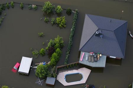 A house with a garden is inundated by the waters of the Elbe river in the village of Fischbeck in the federal state of Saxony Anhalt after it was flooded by the Elbe river June 12, 2013. REUTERS/Thomas Peter
