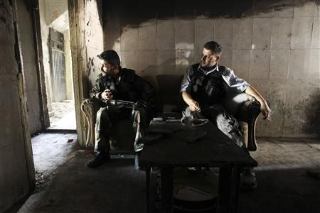 Members of the Free Syrian Army sit on a sofa inside a house in the old city of Aleppo June 19, 2013. REUTERS/Muzaffar Salman
